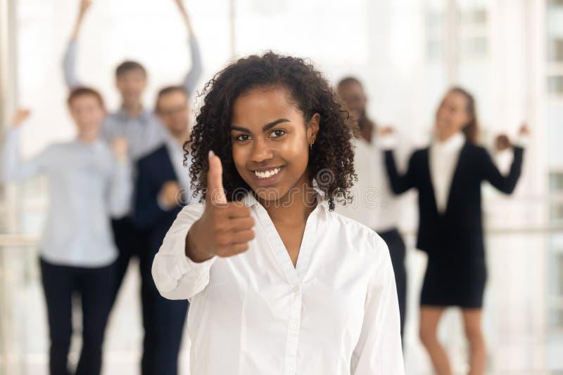 Pulgares que muestran femeninos africanos satisfechos encima de empleados felices en fondo imagen de archivo libre de regalías