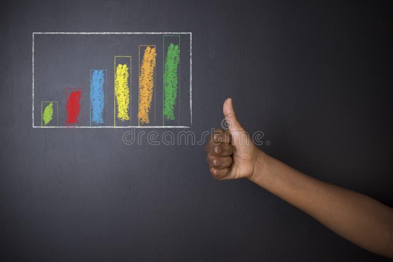 Pulgares surafricanos o afroamericanos del profesor o del estudiante para arriba contra gráfico de barra de la tiza de pizarra fotos de archivo libres de regalías