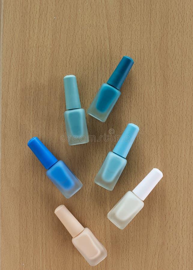 Pulimento de clavos azul en colores pastel en la tabla imagen de archivo