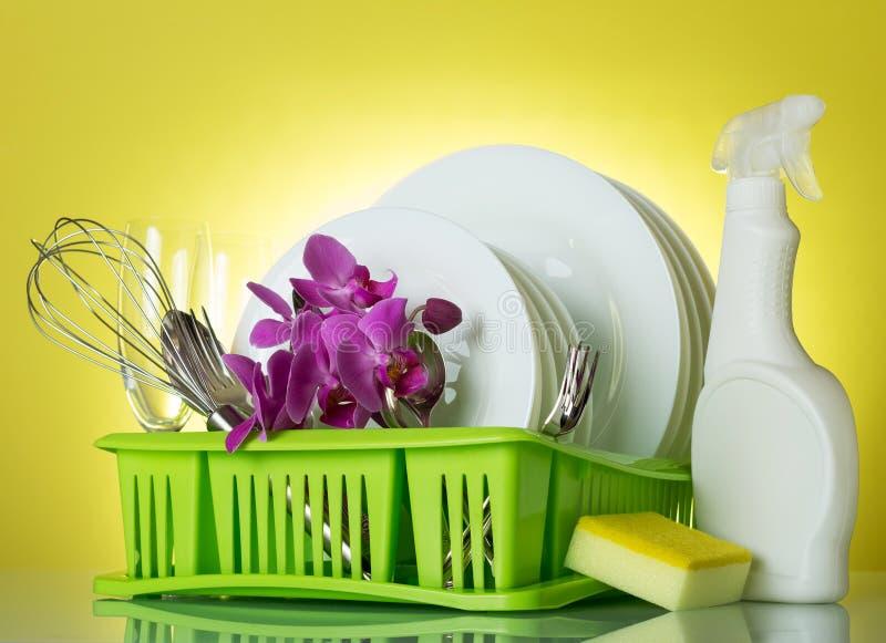 Pulisca i piatti e la coltelleria sull'essiccatore, sul detersivo del piatto e sulla spugna, su fondo giallo fotografia stock libera da diritti