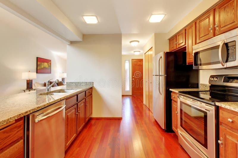 Pulisca la cucina di stile con i gabinetti ed i ripiani di legno del granito fotografia stock libera da diritti