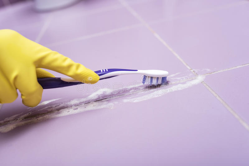 Pulisca le mattonelle con uno spazzolino da denti fotografia stock