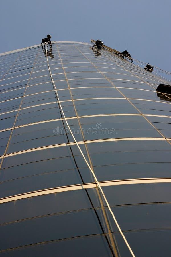 Pulitori di finestra che ciondolano da una corda fotografia stock libera da diritti