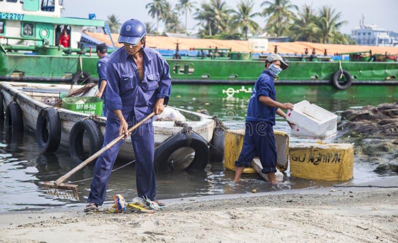 Pulitori locali che puliscono e che portano immondizia sulla spiaggia fotografia stock libera da diritti