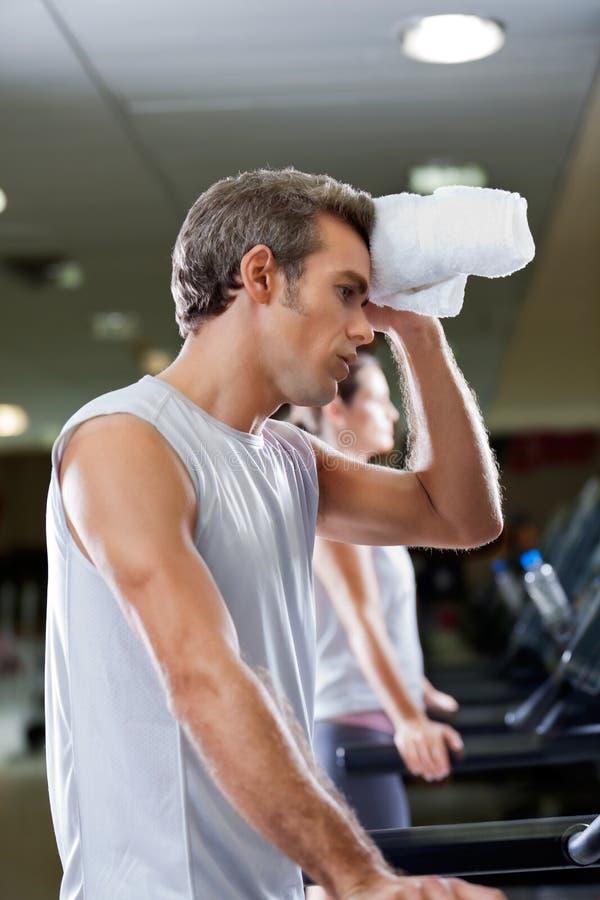 Pulitura dell'uomo sudata con l'asciugamano al club di salute fotografia stock libera da diritti