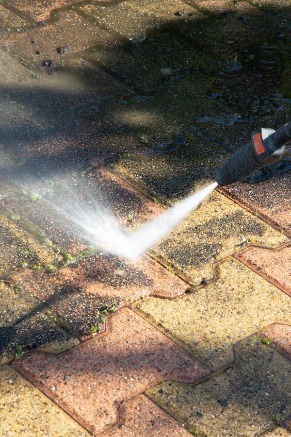 Pulizia all'aperto del pavimento con il getto di acqua ad alta pressione fotografia stock libera da diritti