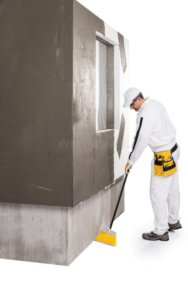 Pulizia del lavoratore con un manico di scopa immagine stock