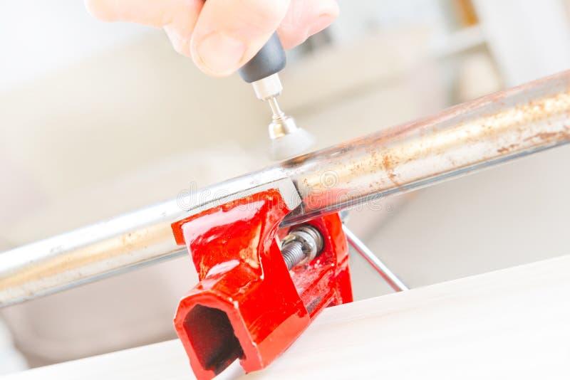 Pulizia del tubo arrugginito con il multi strumento rotatorio fotografie stock