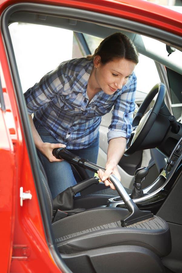 Pulizia della donna dentro dell'automobile facendo uso dell'aspirapolvere fotografia stock