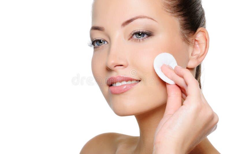 Pulizia della donna di bellezza il suo fronte con il tampone di cotone immagine stock libera da diritti