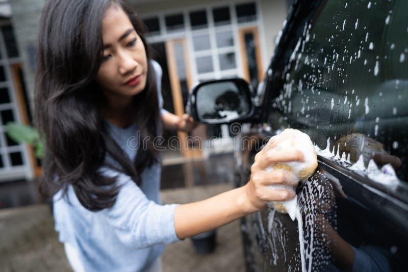 Pulizia della donna e lavare la sua automobile nera fotografia stock libera da diritti