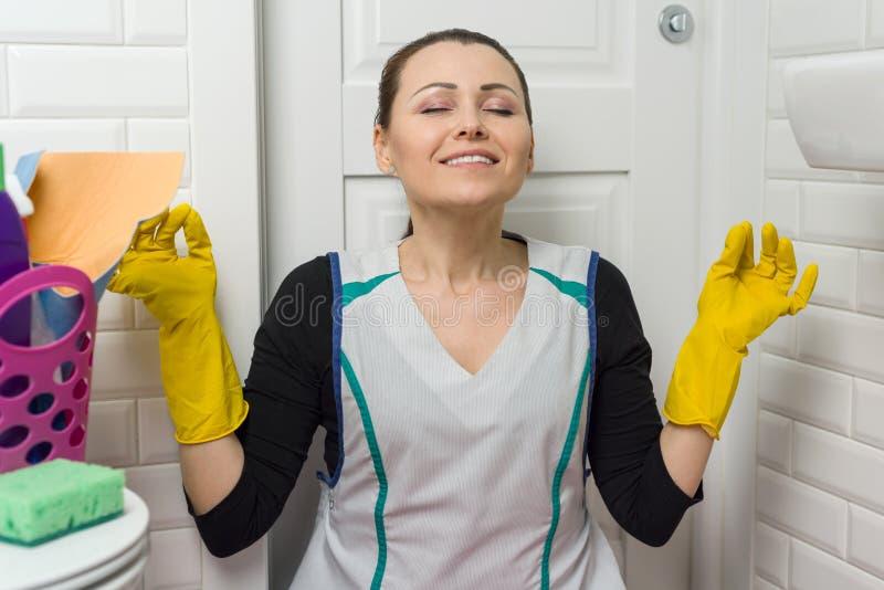 Pulizia della donna nel bagno a casa, stanco, meditando fotografie stock