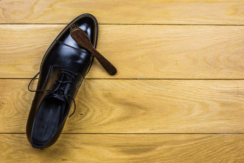 Pulizia della scarpa fissata su fondo di legno immagini stock