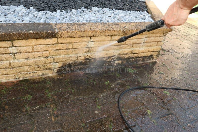 Pulizia esteriore e pulizia della costruzione con l'uomo ad alta pressione del getto di acqua immagine stock libera da diritti