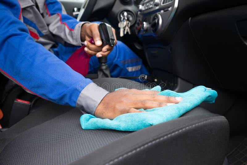 Pulizia Seat del lavoratore dentro l'automobile fotografia stock libera da diritti