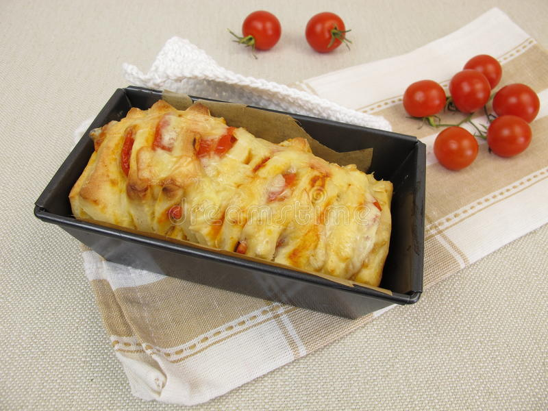Pull-Apart-Bread with tomatoes and cheese in loaf pan stock image