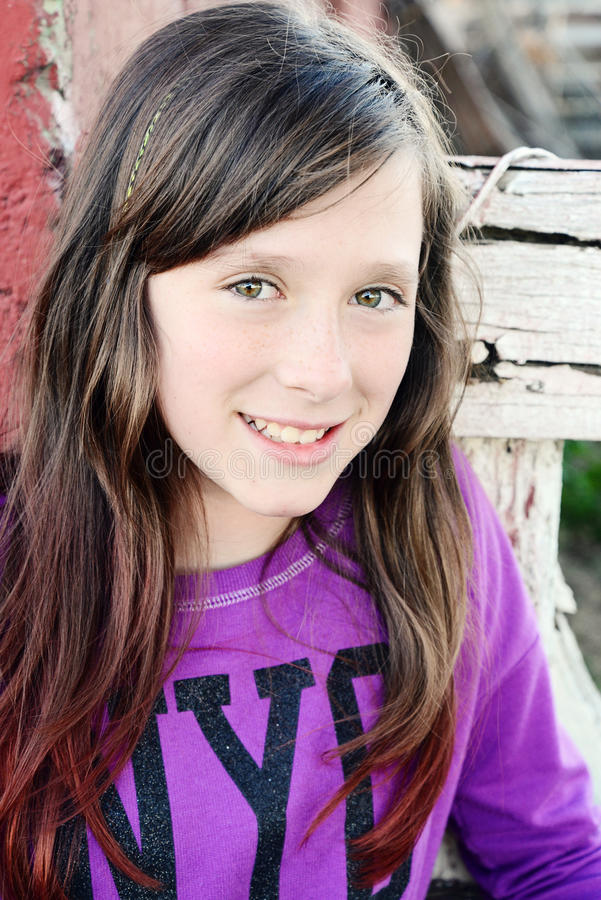Pull molletonné de sourire de mode de jeune fille devant la porte rouge photo stock