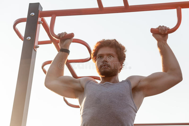 Pull ups in orizontal bars. Young adult bearded redhead man doing pull ups. Outdoor stock photography