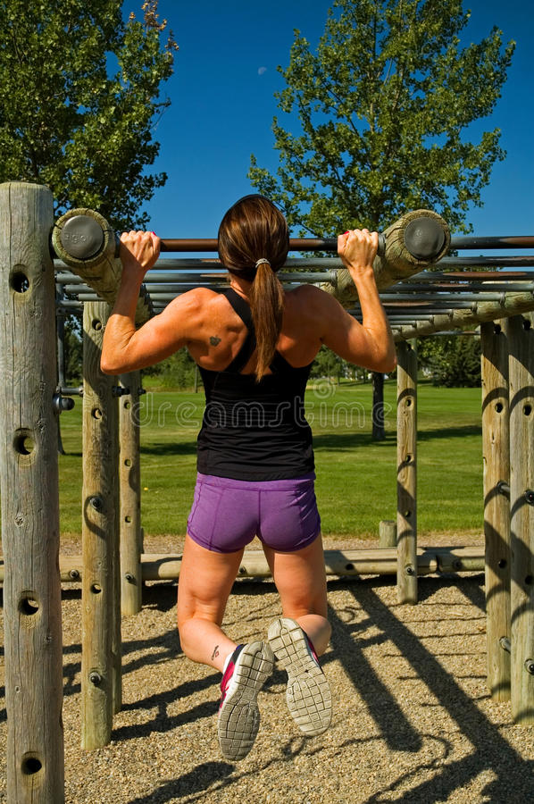 Pull ups. Woman doing pull ups with some playground equipment stock images