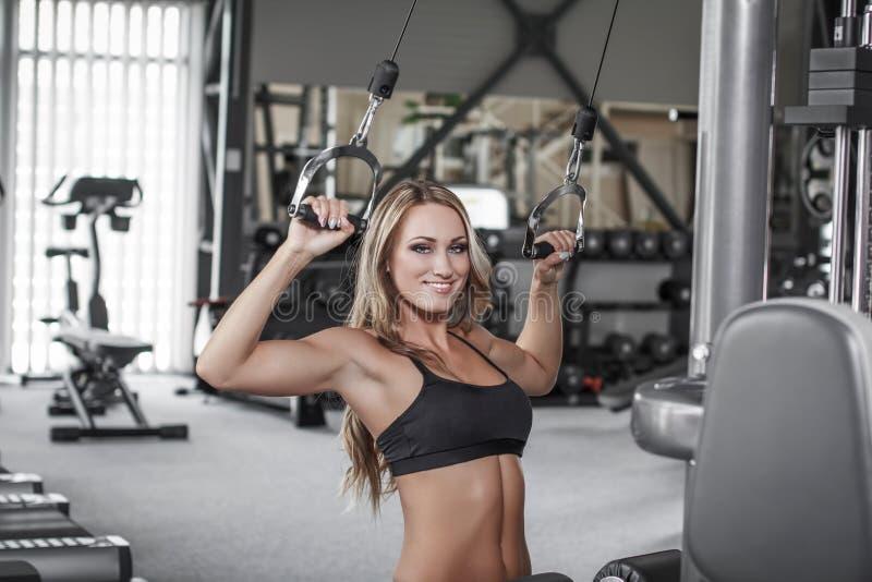 Pulldown van de blonde sexy bodybuilder praktijk in gymnastiek royalty-vrije stock afbeeldingen