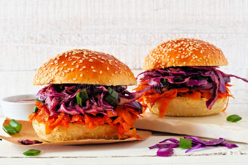 Healthy, plant based meatless pulled carrot burgers against a white wood background. Pulled carrot meatless burgers with red cabbage slaw against a white wood stock images