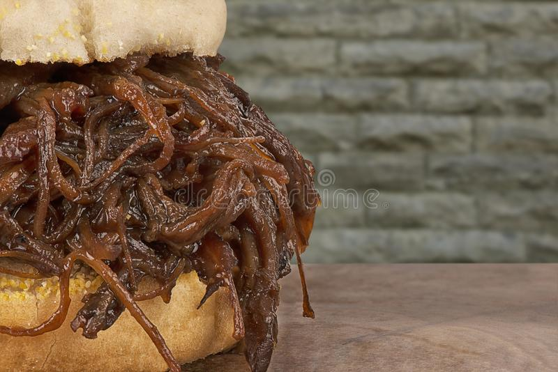 Close up on pulled pork sandwich, wall of brick in background. Pulled pork sandwich, wall of brick in background. Close up on the texture of the meat stock photography