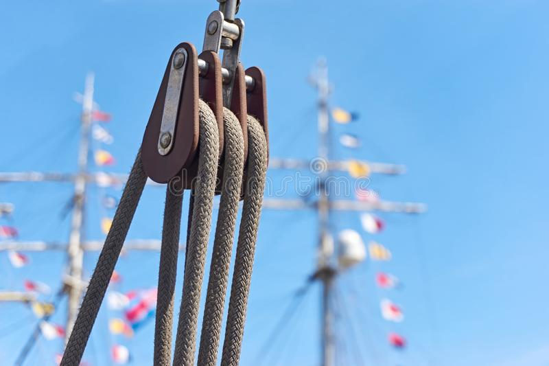 Pulley with ropes against a blue sky and masts with colored flags stock images