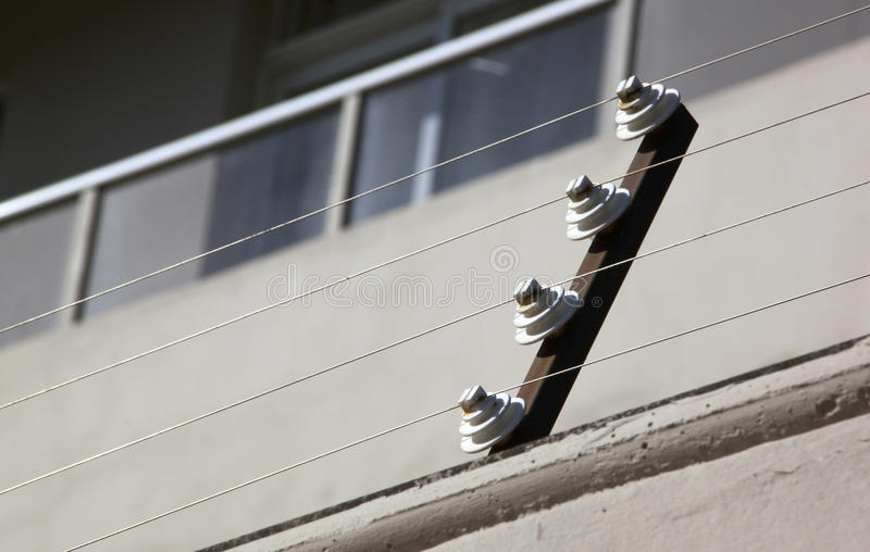 Pulleys Supporting Electric Fence of Residential Building stock photos