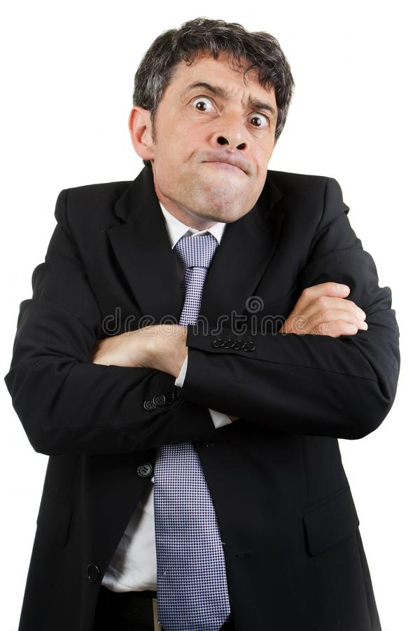 Pulling a face. Businessman is pulling a face with arms crossed stock image