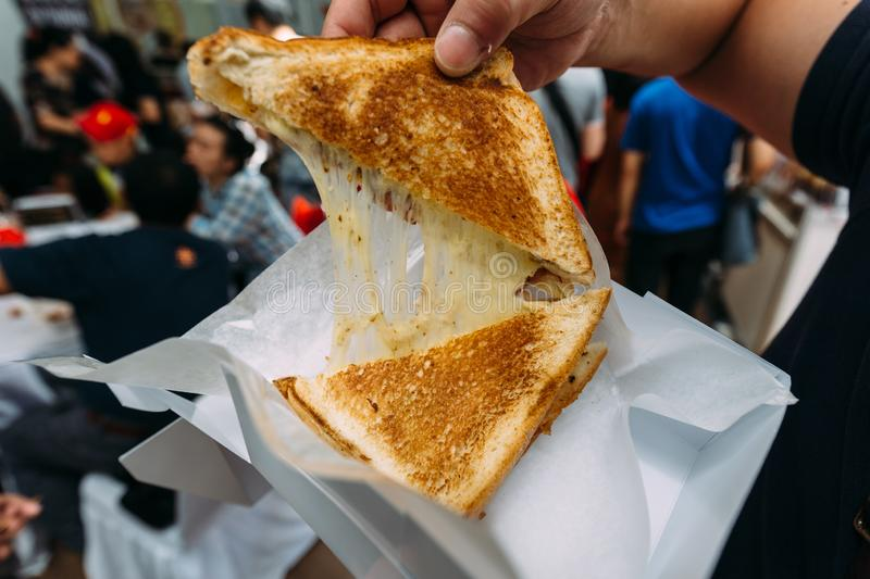 Pulling separate a Grilled Cheese Toast by hand with stretching cheese inside royalty free stock images