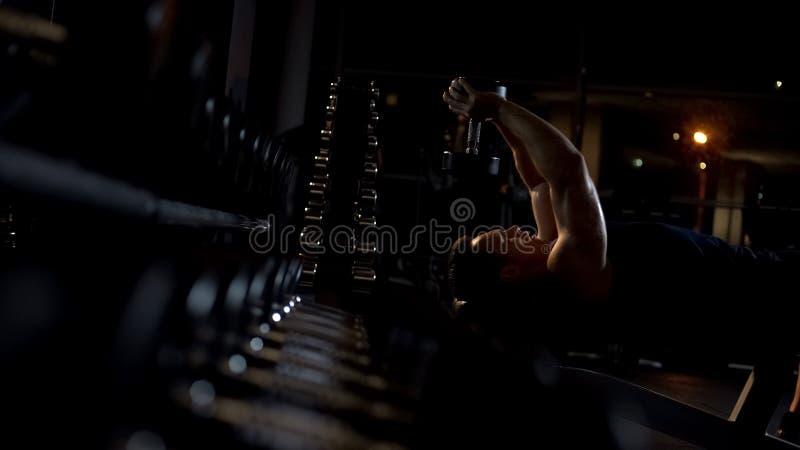 Pullover d'esecuzione della testa di legno dell'atleta utile, trovantesi sul banco, esercizio del petto immagini stock libere da diritti