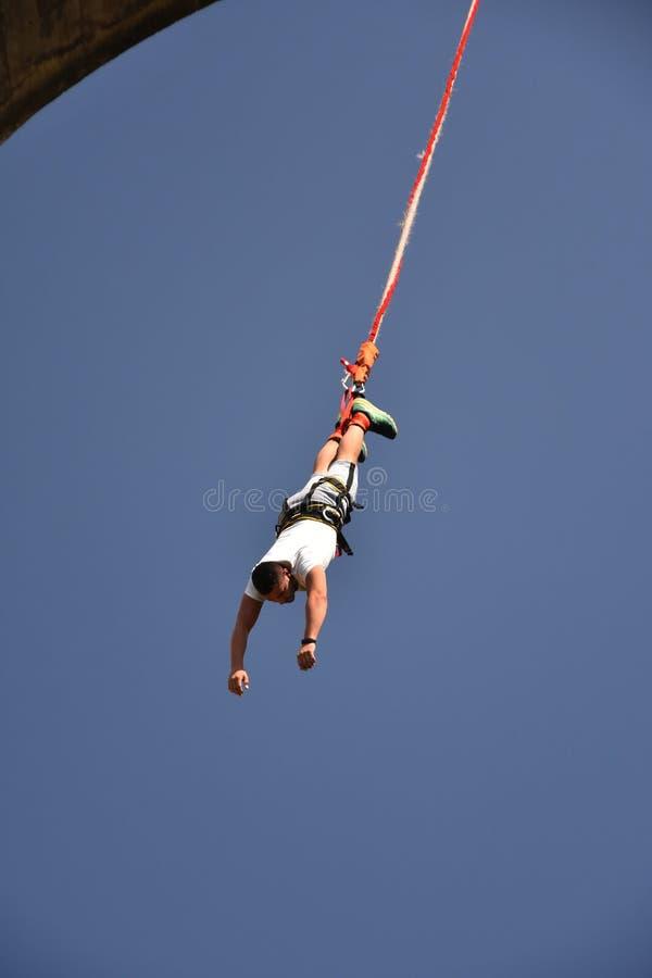 Pullover de bungee de jeune homme accrochant sur une corde photo stock
