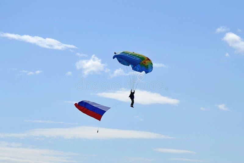 Pullover de parachute sur le fond de ciel bleu avec le drapeau photo stock