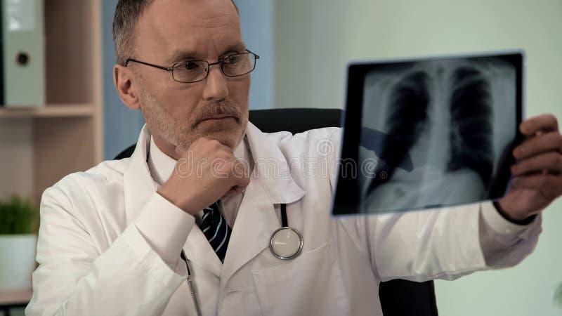 Pulmonologist de sexo masculino que escudriña la radiografía del pecho, buscando la patología, diagnósticos fotos de archivo