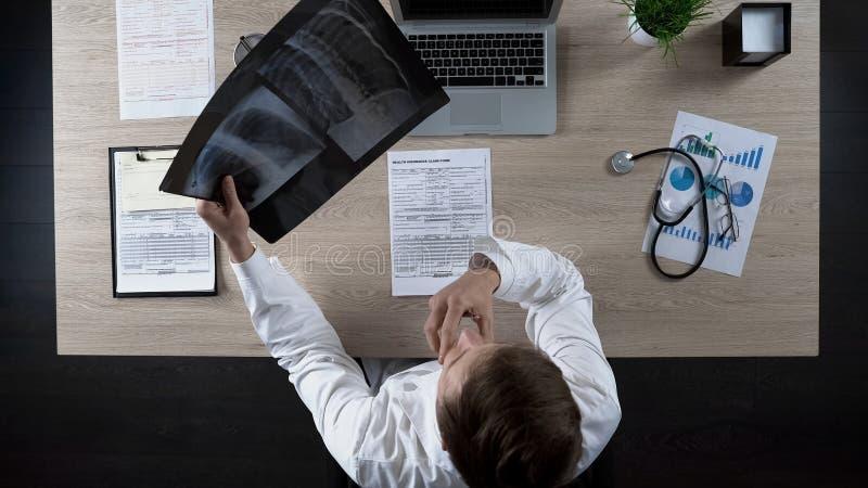 Pulmonologist experimentado que mira la radiografía de los pulmones, reflexionando sobre diagnosis fotos de archivo