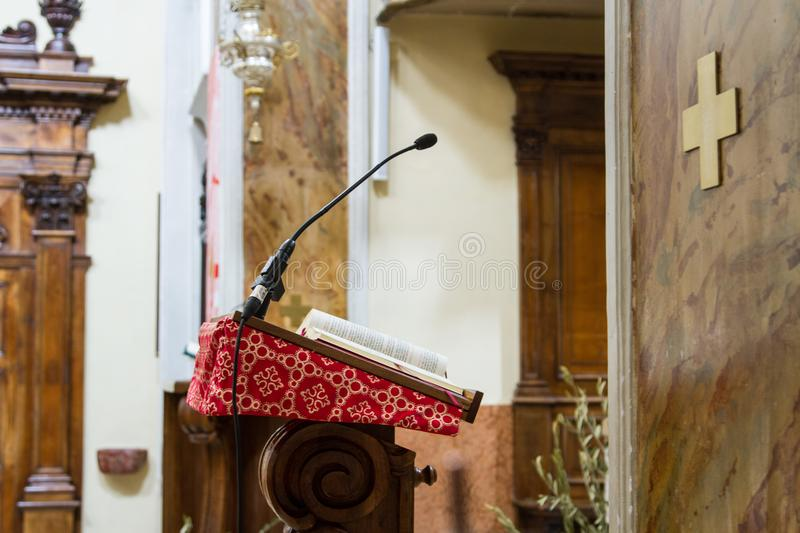 Pulpit in an ancient country church. A pulpit covered with an antique red cloth, with a copy of the holy bible resting on it stock images