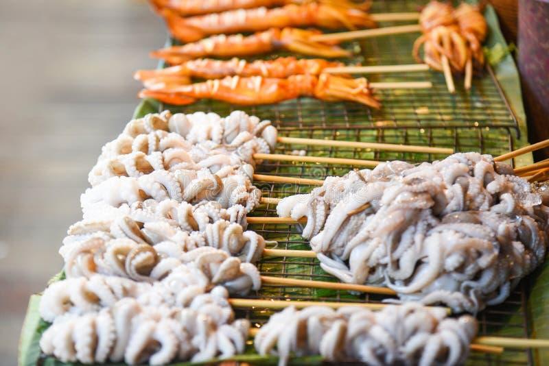 Pulpo asado a la parrilla del calamar en parrilla con los palillos del pincho en la comida de la calle imágenes de archivo libres de regalías