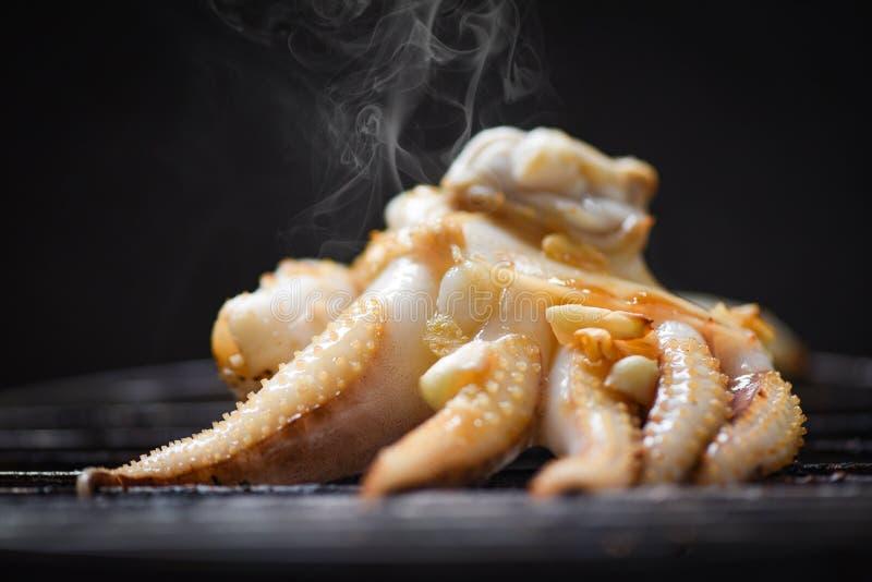Pulpo asado a la parrilla en el Bbq de los mariscos de la parrilla con las hierbas y las especias en fondo oscuro - el calamar de imágenes de archivo libres de regalías