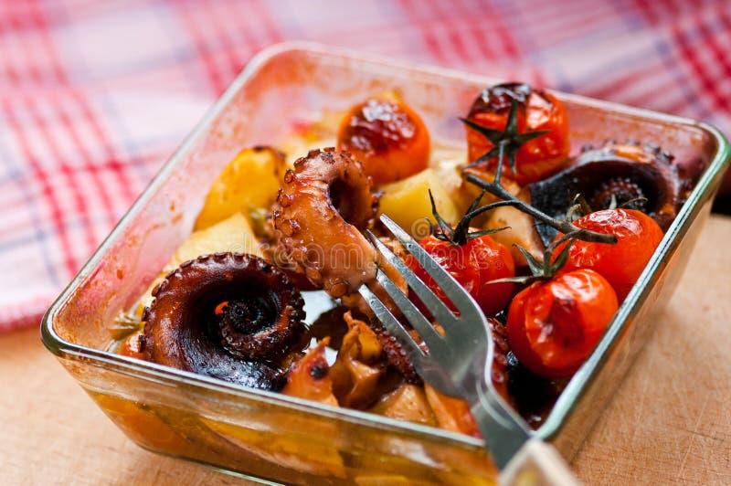 Pulpo fresco cocido con los tomates y las patatas fotos de archivo
