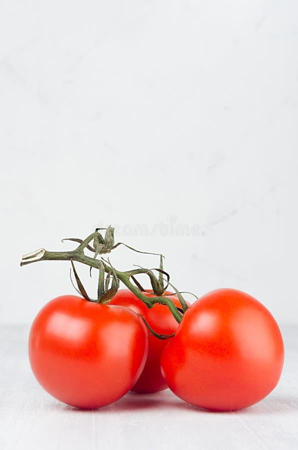 Pulpy κόκκινες ντομάτες στον κλάδο στο ελαφρύ μαλακό άσπρο σύγχρονο εσωτερικό κουζινών με το διάστημα αντιγράφων, κατακόρυφος, κι στοκ φωτογραφίες με δικαίωμα ελεύθερης χρήσης