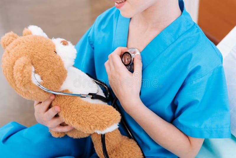 Pulsação do coração de escuta da enfermeira da menina com o urso de peluche como o doutor fotografia de stock royalty free