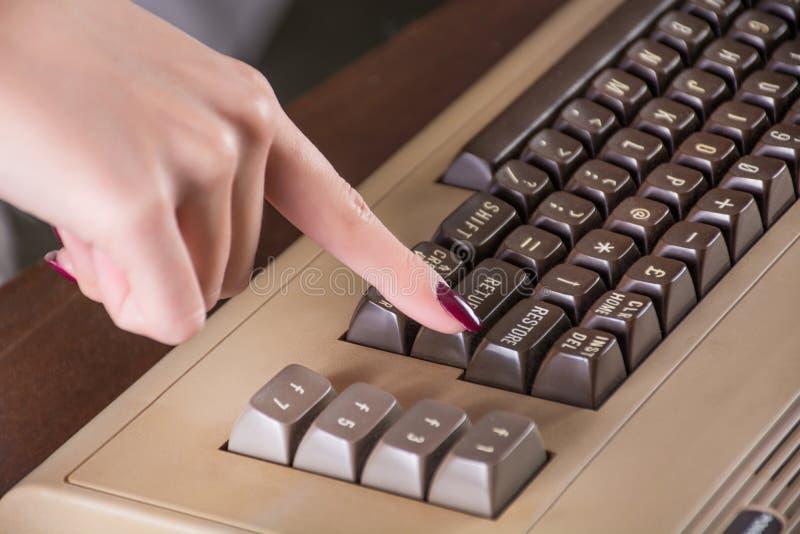 Pulsante del dito della ragazza sulla vecchia tastiera di computer immagine stock libera da diritti