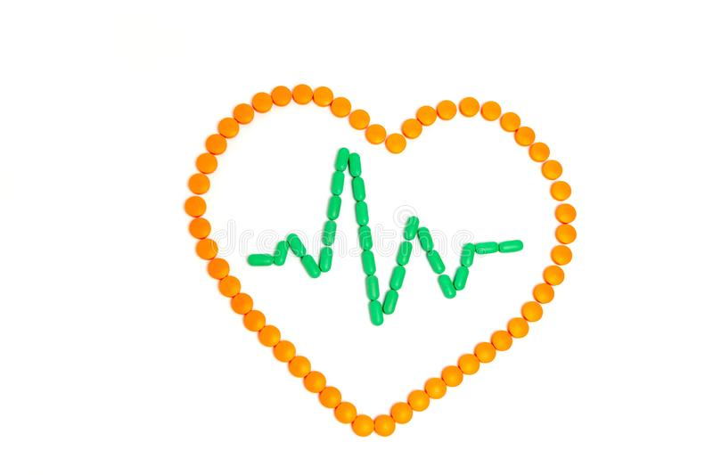 A pulse is by green pills in the orange heart Isolated on white background. Medicine concept stock images