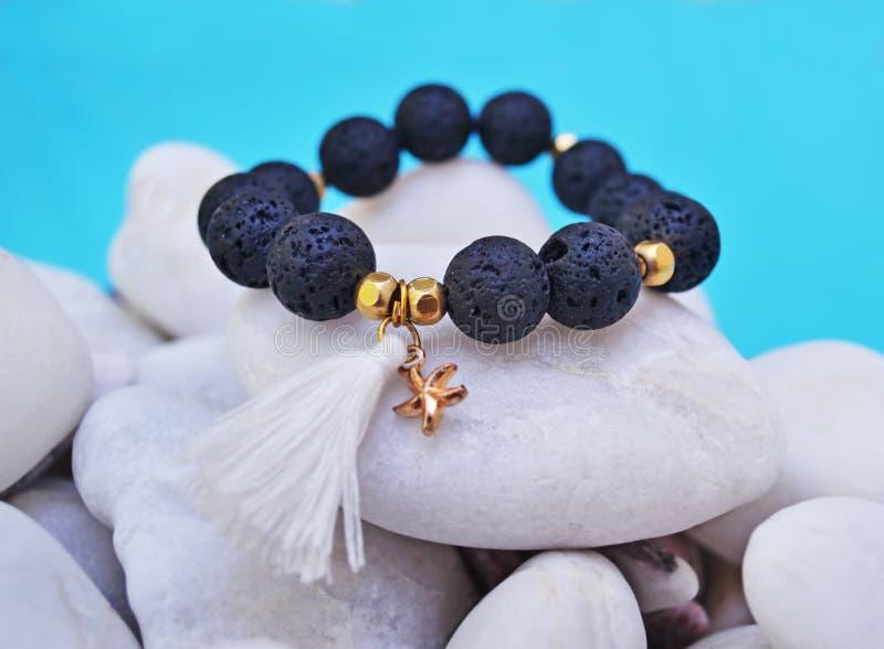 Pulsera de la piedra preciosa con las gotas negras y las estrellas de mar pendientes - piedras de la lava del volcán foto de archivo libre de regalías
