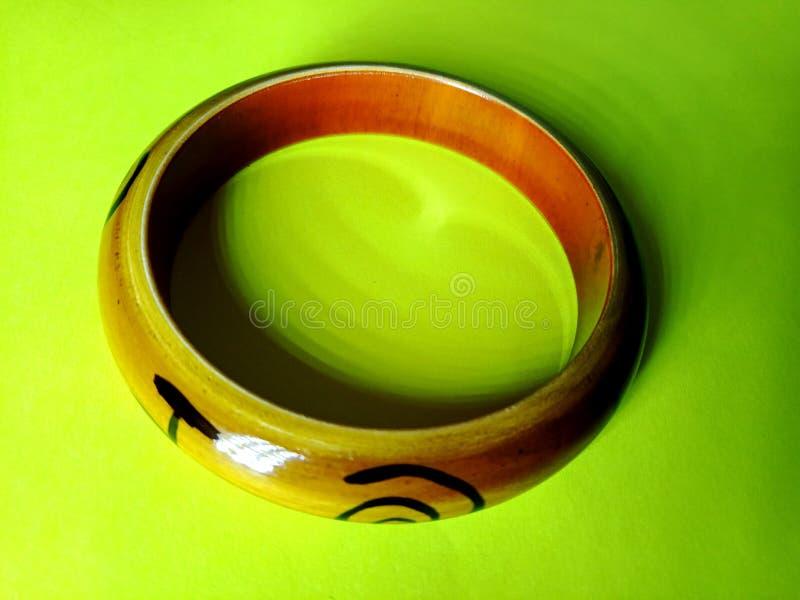 Pulsera de madera Handcrafted aislada en fondo amarillo con el foco ligero de una esquina fotografía de archivo