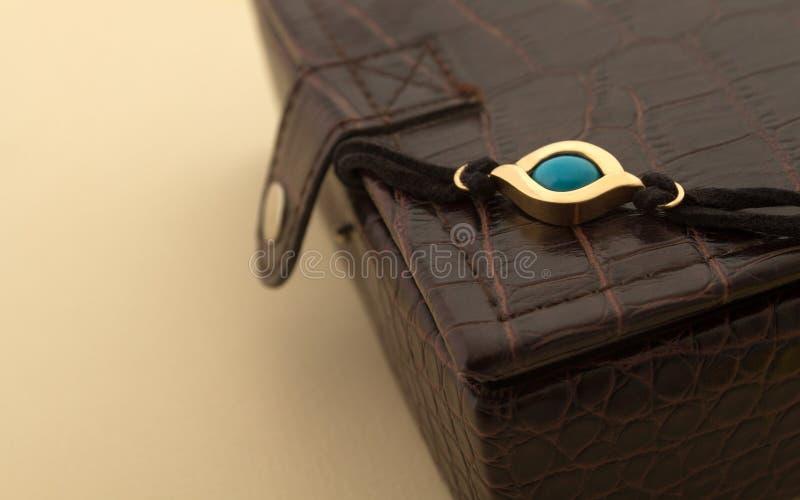 Pulsera de oro del ojo azul en el joyero de cuero imágenes de archivo libres de regalías