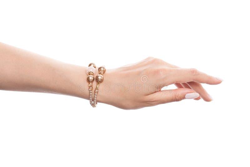Pulsera de oro de la joyería con las perlas en la mano femenina aislada en el fondo blanco fotografía de archivo libre de regalías