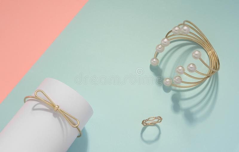Pulsera de oro de la perla y anillo de oro en fondo del color en colores pastel con el espacio de la copia imagen de archivo libre de regalías