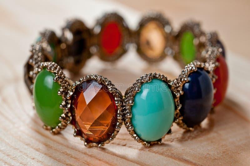 Pulsera de piedras coloreadas brillantes en un fondo de madera imagen de archivo