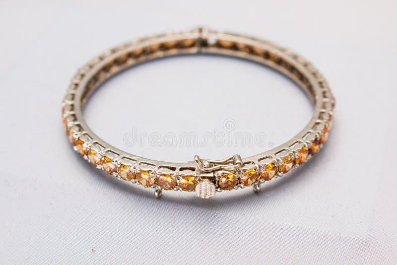 Pulsera delgada hermosa del oro y de la plata con las piedras preciosas brillantes fotografía de archivo libre de regalías